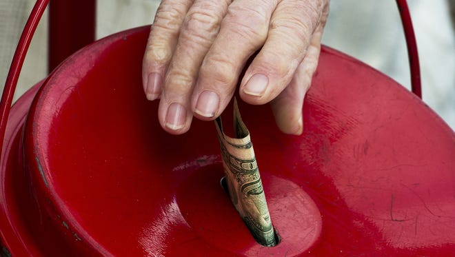 A woman makes a donation into a Salvation Army kettle outside a Giant grocery store in Clifton, Va.
