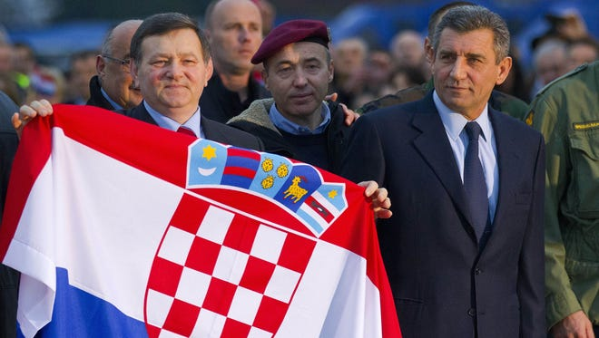Freed Croatian Gen. Ante Gotovina, right and Gen. Mladen Markac hold the Croatian flag upon their arrival to the airport in Zagreb, Croatia, Friday, Nov. 16, 2012.