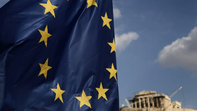 A European Union flag with the Parthenon in the far background in Athens.