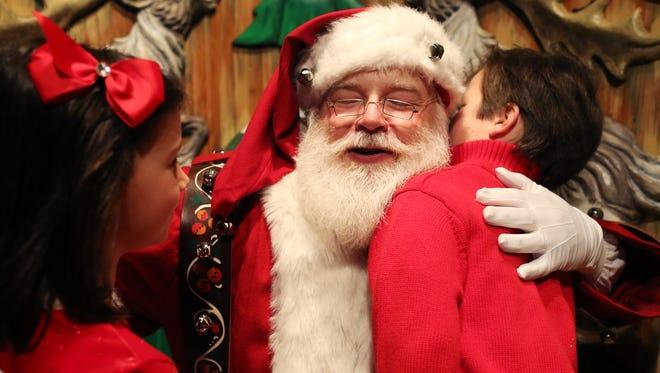 Santa Claus hugs a young visitor at Macy's Santa Land at the 34 Street Herald Square store in New York.