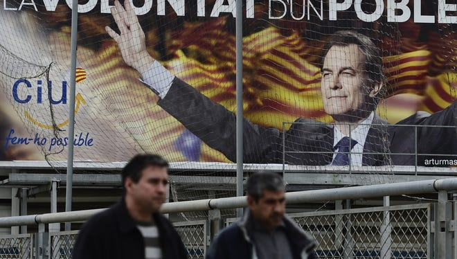 Two men walk in front of an election poster featuring the leader of the center-right Catalan Nationalist Coalition, Artur Mas, in Barcelona, Spain, on Monday.