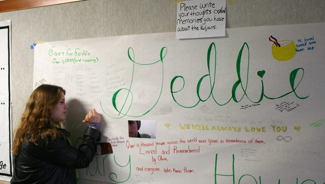Arcata High School student Blaire Floyd writes on a poster memorial for fellow student Gregory Kulijian. The 16-year-old boy is missing after trying to rescue his dog from surging surf near San Francisco. His parents drowned trying to save him Saturday.