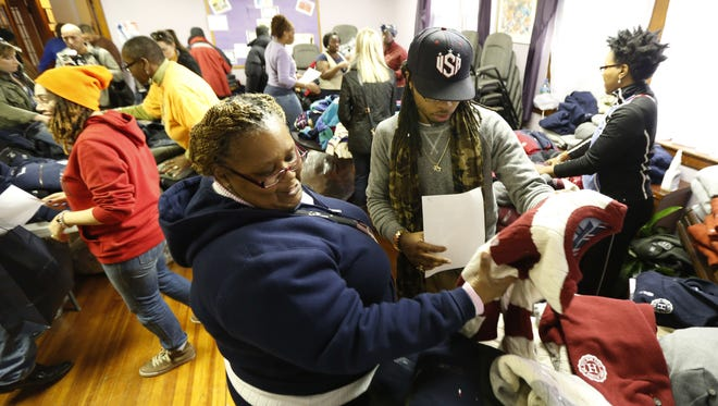 Valerie Jones, left, is helped by volunteer Jaraun Wright on Nov. 9 as she picks out donated clothing at Clinton Hill Community Resource Center in Newark, one of the cities hit hard by Superstorm Sandy.