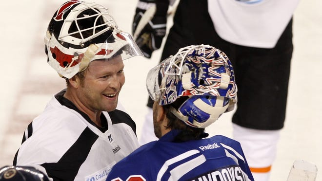 Henrik Lundqvist, right, greeting Martin Brodeur after the game, said he was impressed by the attitude of the storm victims who attended the game.