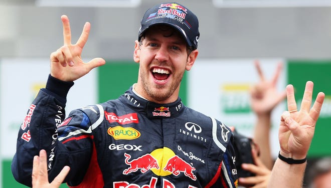 Sebastian Vettel celebrates with teammates as he clinches his third consecutive drivers world championship during the Brazilian Grand Prix.