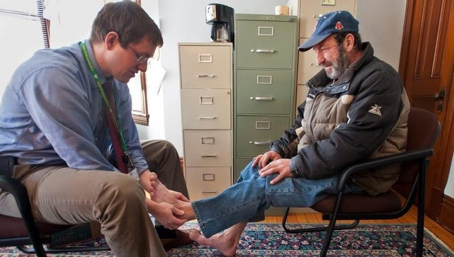 Edward Badeau of Burlington, Vt., right, has his feet examined by Michael Wright, an orthopedic resident at Fletcher Allen Health Care, at a Committee on Temporary Shelter facility.