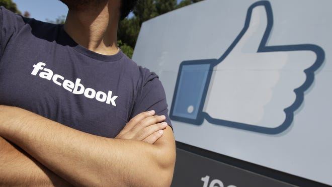 A Facebook worker waits for friends to arrive outside Facebook headquarters in Menlo Park, Calif.