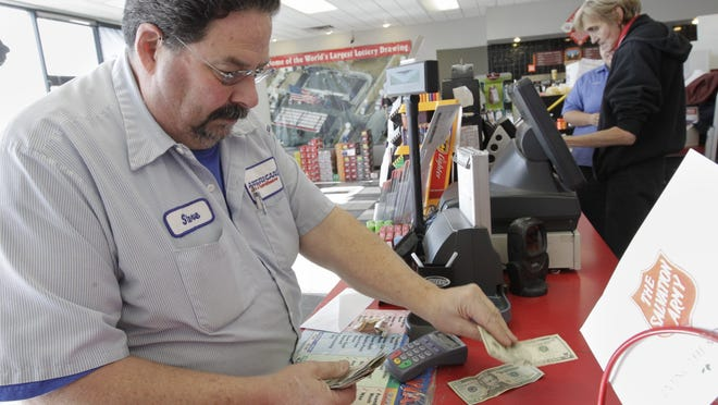 Steve Bowen, on behalf of ten co-workers, buys powerball lottery tickets at the U-Stop convenience store in Lincoln, Neb., Tuesday. The jackpot has grown to over $500 million.