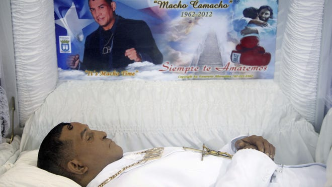 "The body of former boxing champion Hector ""Macho"" Camacho lies in an open casket during his funeral in San Juan, Puerto Rico, on Tuesday. Hundreds of people took pictures and filed past Camacho's open casket displayed inside a gymnasium."