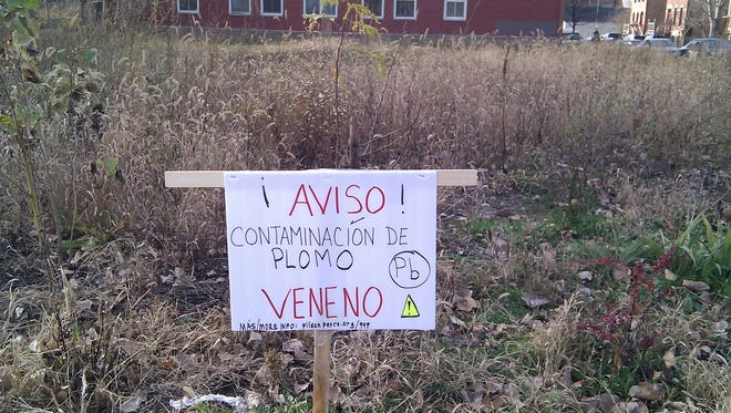 A warning sign posted by community activists sits on the property of an old lead factory in Chicago.