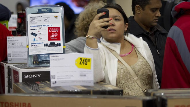 A shopper uses her smartphone to shop for bargains at the Best Buy in Pembroke Pines, Fla, on Thursday, Nov. 22, 2012.