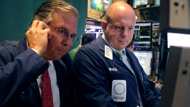 Michael O'Connor, right, of Getco Securities works on the floor of the New York Stock Exchange in this file photo.