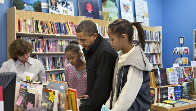 President Barack Obama, with daughters Sasha, left, and Malia, right, goes shopping at a small bookstore, One More Page, in Arlington, Va., on Saturday, Nov. 24, 2012.