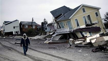 A man walks past destroyed homes on the Rockaway Peninsula in Queens, New York, on Tuesday. Delegates are meeting in Qatar to discuss ways of slowing climate change, including cutting emissions of greenhouse gases that scientists say are warming the planet and exacerbating storms.