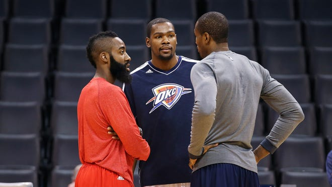 Houston Rockets shooting guard James Harden (left) speaks with Oklahoma City Thunder small forward Kevin Durant (right) and Oklahoma City Thunder power forward Serge Ibaka (right) before the game at Chesapeake Energy Arena.