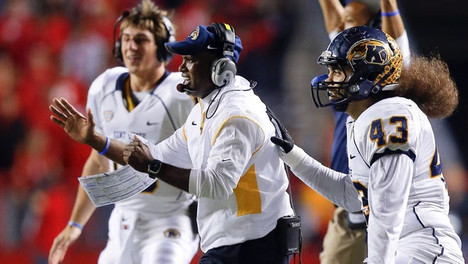 Kent State coach Darrell Hazell, center, celebrates a win over Rutgers that helped the Golden Flashes sustain a remarkable turnaround of their football fortunes this season.