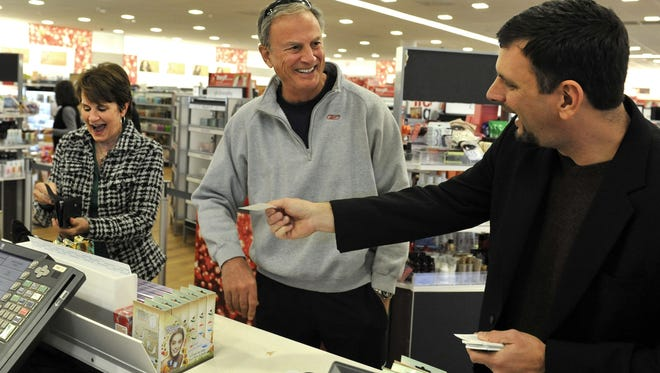"""Asheville Mall general manager Jeff Washburn, right, surprises shoppers Emily, left, and Blair Ferguson with a """"random act of kindness"""" offering to pay for their purchases at Ulta in Asheville, N.C., on Wednesday, Nov. 28, 2012."""