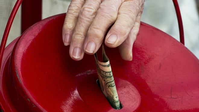 A woman puts a donation Saturday into a Salvation Army kettle outside a grocery store in Clifton, Va.