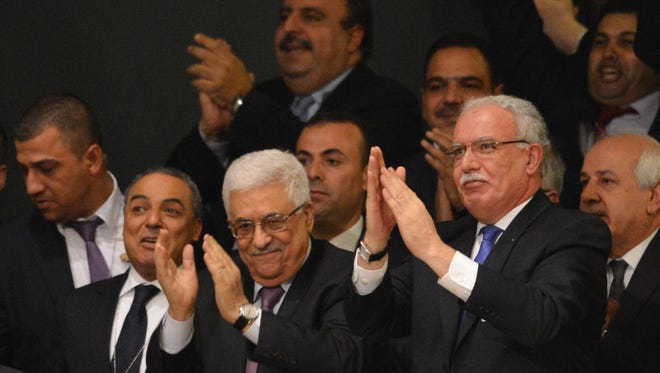 Palestinian Authority President Mahmoud Abbas, center, and the delegation celebrate after the United Nations General Assembly voted to approve a resolution to upgrade the status of the Palestinian Authority to a non-member observer state Thursday.