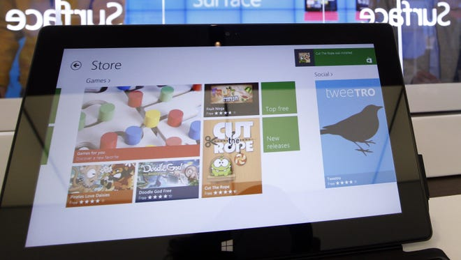 Customers look at the Microsoft Surface tablet at a Microsoft store in Seattle.
