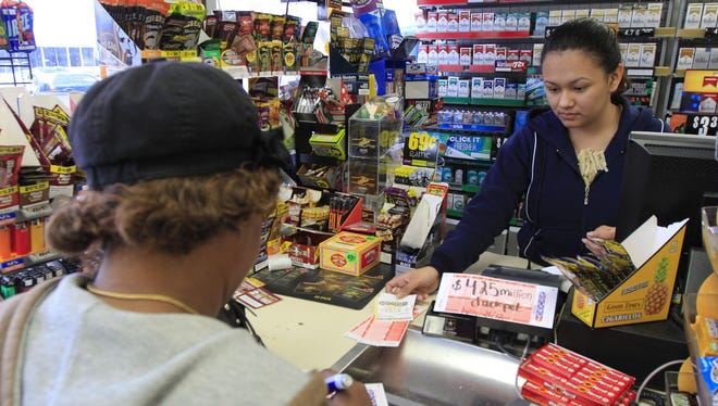 Roselyn Jones purchases a few Powerball tickets from a station attendant at the Conoco Sunrise Market off of Brainerd Road in Chattanooga, Tenn.
