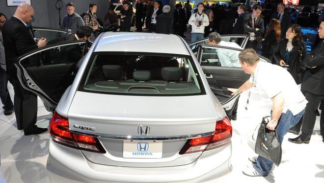 Reporters examine the new interior of the Honda Civic EX Sedan