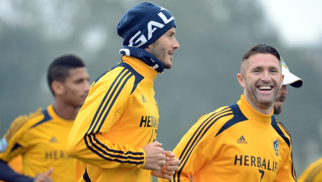 David Beckham, wearing knit cap, and Robbie Keane  warm up for the Los Angeles Galaxy in preparation for the MLS Cup at The Home Depot Center on Saturday.