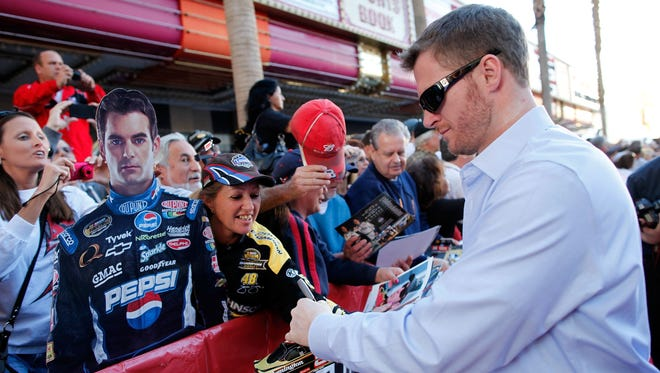 Dale Earnhardt Jr. gives Junior Nation some ink during NASCAR Fanfest at the Fremont Street Experience on Wednesday in Las Vegas.