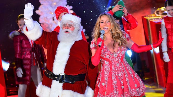 Santa Claus and Mariah Carey perform during a pre-tape performance for NBC's Christmas tree lighting at Rockefeller Center on November 27, 2012 in New York.