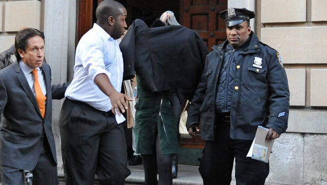 Lindsay Lohan, second from right, is escorted from the 10th Precinct police station, with her face shielded, today, in New York.