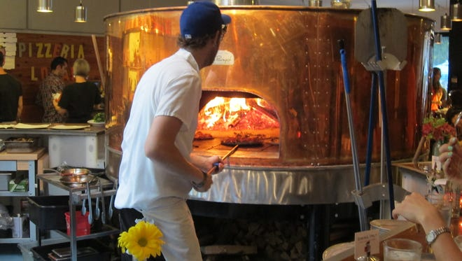 The wood-fired pizza oven resembles a brewery tank.