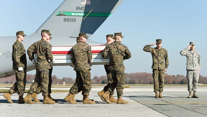 A Marine Corps team transfers the remains of a fallen comrade at Dover Air Force Base, Del.
