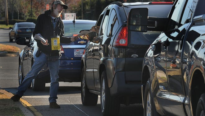 Homeless man Brian Wolz sells the Contributor newspaper to motorists along a street in Franklin, Tenn.