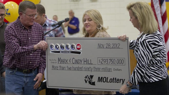 Mark, left, and Cindy, center, Hill are presented a check by a Missouri Lottery official during the announcement of Powerball winners in Dearborn, Mo.