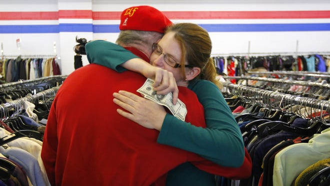 Janice Kennedy hugs Secret Santa after getting a $100 dollar bill from the wealthy philanthropist from Kansas City, Mo.