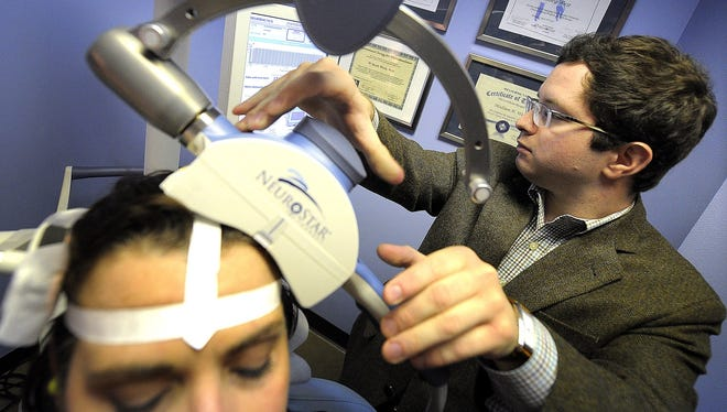 A patient is fitted for transcranial magnetic stimulation by Madison West in Nashville.