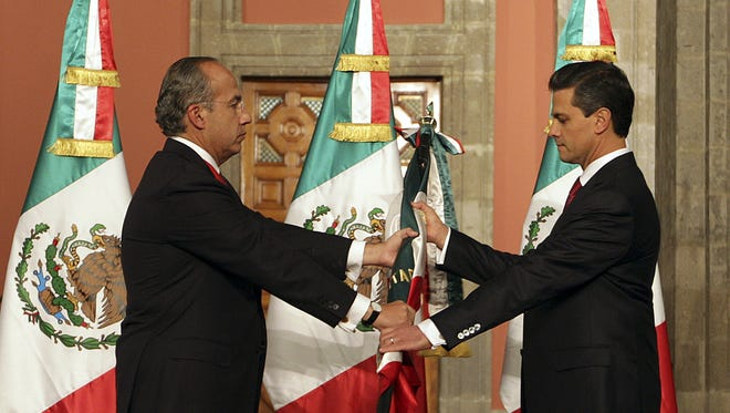 Mexico's outgoing president, Felipe Calderon, left, gives a Mexican flag to president-elect Enrique Pena Nieto during the official transfer of command ceremony at the National Palace in Mexico City.