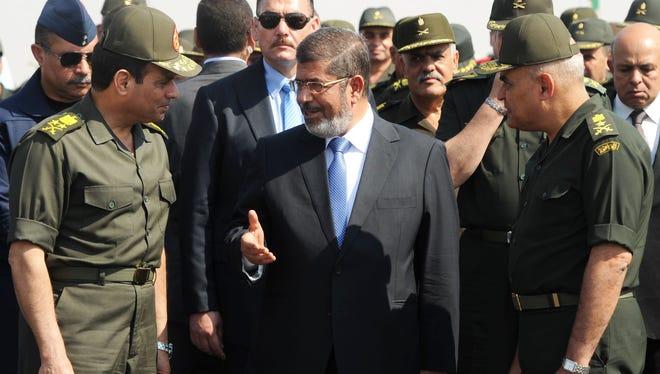 Egyptian President Mohammed Morsi, center, speaks with Egypt's minister of Defense, Lt. Gen. Abdel-Fattah el-Sissi, left, at a military base in Ismailia, Egypt, on Oct. 10.