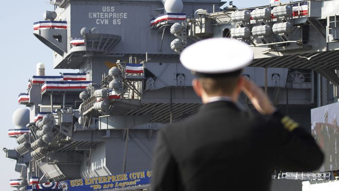 A Navy officer salutes during the inactivation ceremony for the USS Enterprise at Naval Station in Norfolk, Va., on Saturday.