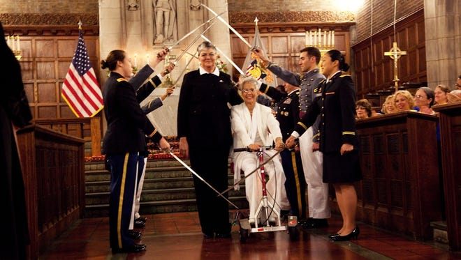 Brenda Sue Fulton and Penelope Gnesin move though the traditional saber arch during their wedding Saturday at West Point.
