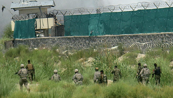 In this 2010 photo, U.S. and Afghan soldiers walk the perimeter of a major NATO base in Jalalabad, eastern Afghanistan.