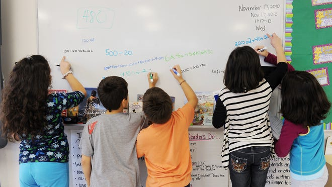 Fourth graders work at the whiteboard during math class at Stark Elementary School in Stamford, Conn., on Nov. 17, 2010.