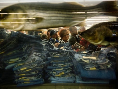 Shoppers pick through stacks of discounted jeans during the 2012 holiday shopping season. Canadian tour operators have brought shoppers down to the U.S. to take advantage of the deals that aren't available in Canada.