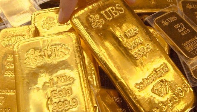 A South Korean employee shows a gold bar at Shinhan Bank in Seoul.