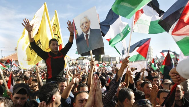 Palestinians wave flags and pictures of Palestinian President Mahmoud Abbas as they celebrate their successful bid to win U.N. statehood recognition in the West Bank city of Ramallah on Sunday.