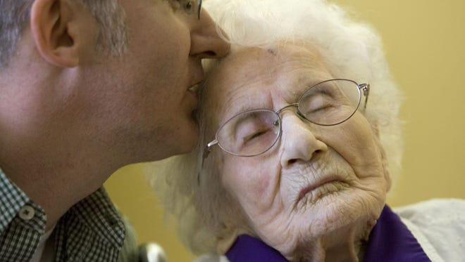 Besse Cooper, right, receives a kiss from her grandson Paul Cooper, 42, during a ceremony in which Guinness World Records recognized her as the world's oldest living person in 2011.