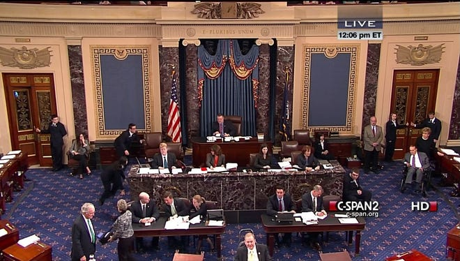 This video image provided by C-SPAN 2 shows former senator Bob Dole, right, wheeled into the Senate Chamber on Tuesday.
