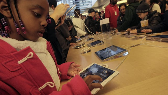 A young girl at Apple's flagship store in New York tries an iPad Min.