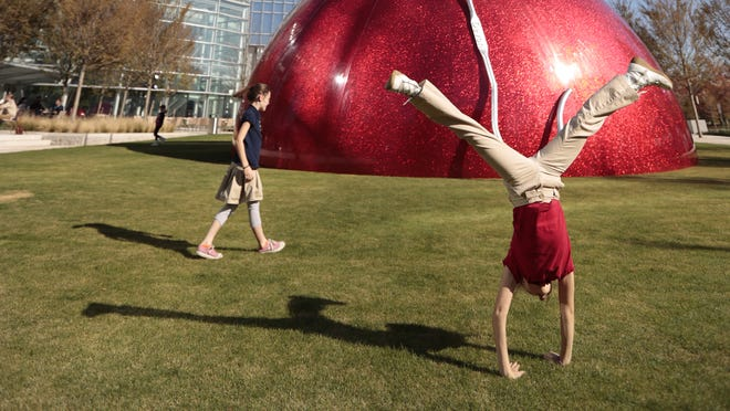 Ella Kibblewhite-Claus, 10, right, and her sister Matariki, 8, play on the south public lawn of the newly opened Devon Energy Center.