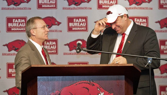 Arkansas Razorbacks athletic director Jeff Long looks on as newly named head football coach Bret Bielema puts on a hat during a press conference to announce his hiring at the University of Arkansas.
